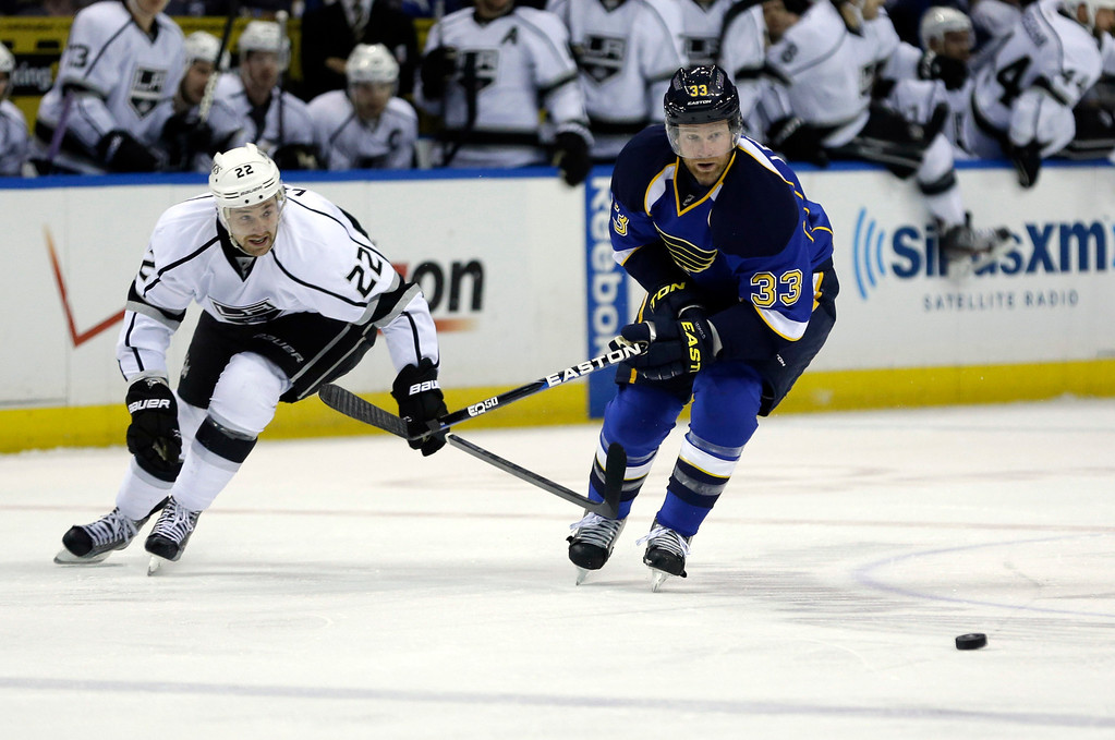 . St. Louis Blues\' Jordan Leopold, right, and Los Angeles Kings\' Trevor Lewis chase after a loose puck during the first period in Game 5 of a first-round NHL hockey Stanley Cup playoff series, Wednesday, May 8, 2013, in St. Louis. (AP Photo/Jeff Roberson)