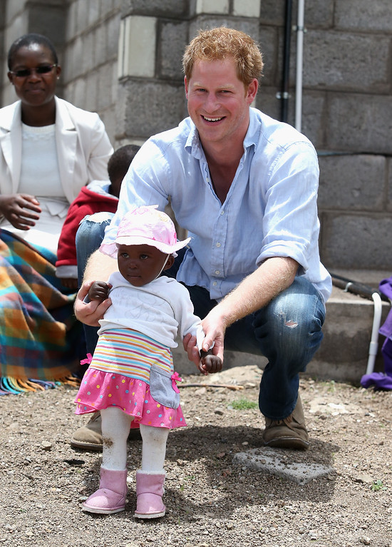 . Prince Harry holds a baby during a visit to a herd boy night school constructed by Sentebale on December 8, 2014 in Mokhotlong, Lesotho. Prince Harry was visiting Lesotho to see the work of his charity Sentebale.  (Photo by Chris Jackson/Getty Images for Sentebale)