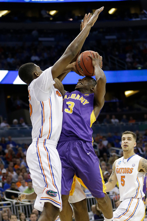 . Florida forward DeVon Walker, left, blocks a shot to the basket by Albany guard DJ Evans (3) in a second-round game in the NCAA college basketball tournament on Thursday, March 20, 2014, in Orlando, Fla. (AP Photo/John Raoux)