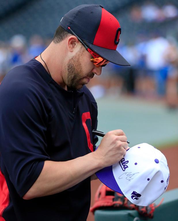 . Cleveland Indians\' Jason Kipnis autographs a purple Kansas City Royals hat before a baseball game at Kauffman Stadium in Kansas City, Mo., Friday, June 2, 2017. It was Kansas State University night at the stadium. (AP Photo/Orlin Wagner)