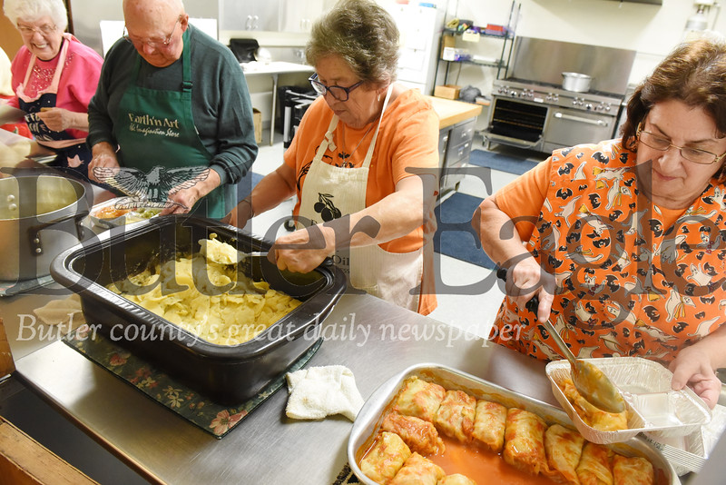 Harold Aughton/Butler Eagle: Left - right, Norah Collins, Fred Berns, Karen Shultz and Roberta McCaslin volunteerd to fill food containers for delivery Thurs., Oct. 31.