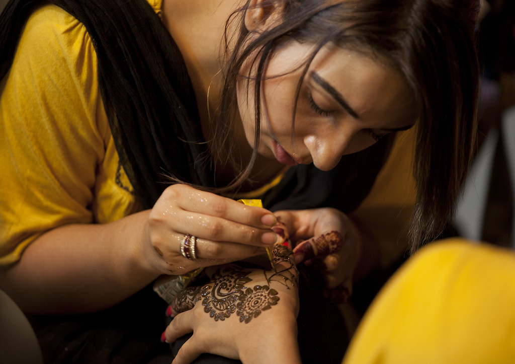 . A Pakistani beautician paints a hand of a customer with henna ahead of the Muslim Eid al-Fitr holiday in Islamabad, Pakistan on Thursday, Aug. 8, 2013. Pakistani Muslims will start celebrating the Eid al-Fitr holiday Friday that marks the end of the holy fasting month of Ramadan. (AP Photo/B.K. Bangash)