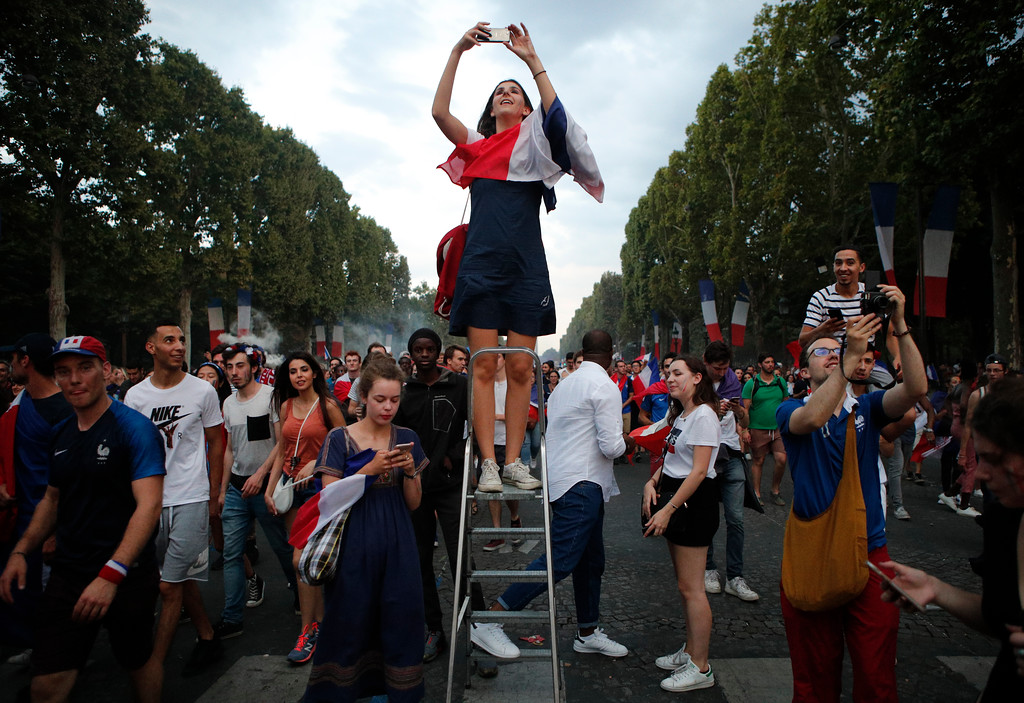 . A woman takes a photo on the Champs Elysees avenue after France won the soccer World Cup final match between France and Croatia, Sunday, July 15, 2018 in Paris. France won its second World Cup title by beating Croatia 4-2 . (AP Photo/Francois Mori)