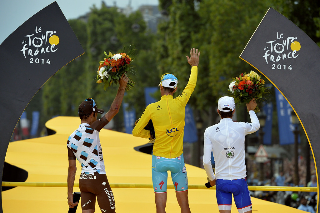 . Tour de France 2014\'s winner Italy\'s Vincenzo Nibali (C), second-placed France\'s Jean-Christophe Peraud (R) and third-placed France\'s Thibaut Pinot (L) wave on the podium on the Champs-Elysees avenue in Paris, at the end of the 137.5 km twenty-first and last stage of the 101st edition of the Tour de France cycling race on July 27, 2014 between Evry and Paris.   ERIC FEFERBERG/AFP/Getty Images