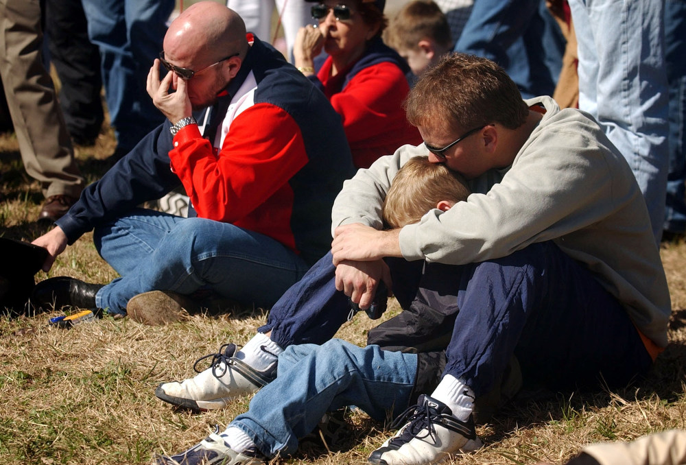 . LYNDON B. JOHNSON SPACE CENTER HOUSTON, TEXAS James Watson, of Montgomery, Texas wipes away a tear as Eddie Langston (right) kisses his 6-year-old son Eric Langston as they  listen via   a television audio  feed  to the memorial service for space shuttle Columbia astronauts going on with President Bush inside the center on Tuesday, February 4, 2003.  Bush was  talking about the astronauts during this moment. CYRUS MCCRIMMON, The Denver Post