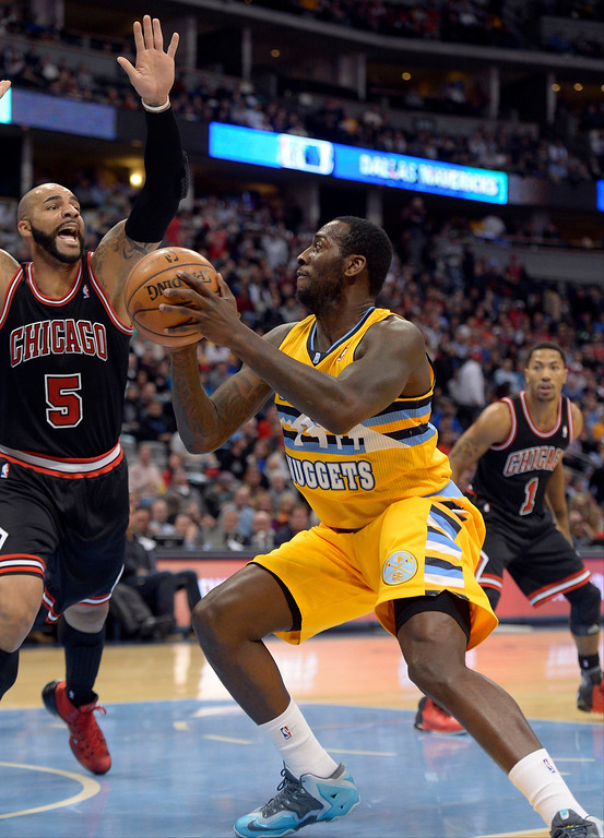 . Denver Nuggets power forward J.J. Hickson (7) puts a move on Chicago Bulls power forward Carlos Boozer (5) as he drives to the basket for a layup during the first quarter November 21, 2013 at Pepsi Center. (Photo by John Leyba/The Denver Post)