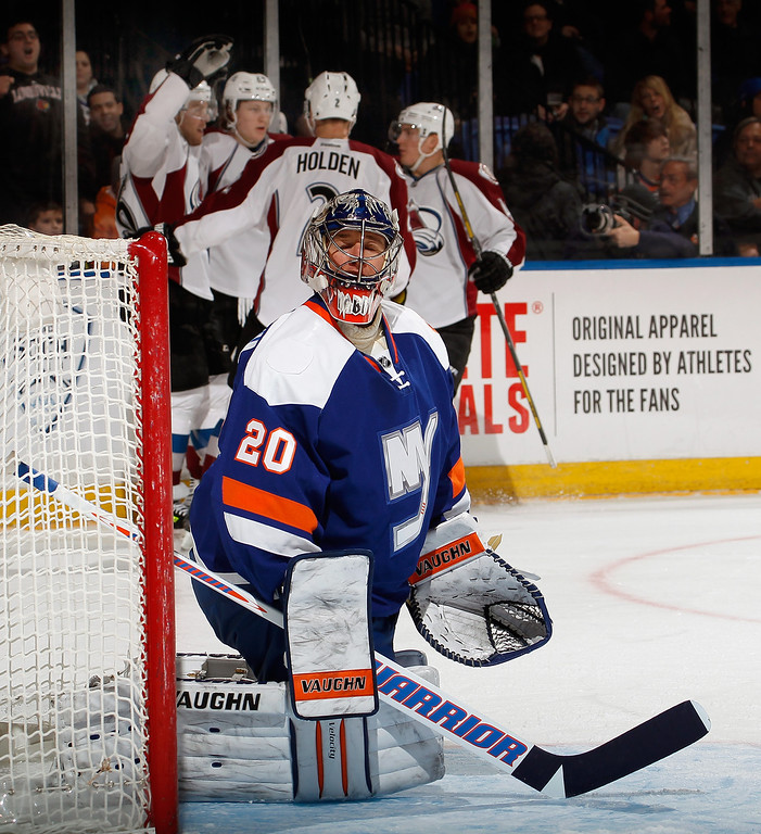 . UNIONDALE, NY - FEBRUARY 08:  Goalie Evgeni Nabokov #20 of the New York Islanders looks up after giving up the first goal of the game as Nathan MacKinnon #29 of the Colorado Avalanche celebrates scoring with teammates in the background during the first period of an NHL hockey game at Nassau Veterans Memorial Coliseum on February 8, 2014 in Uniondale, New York.  (Photo by Paul Bereswill/Getty Images)