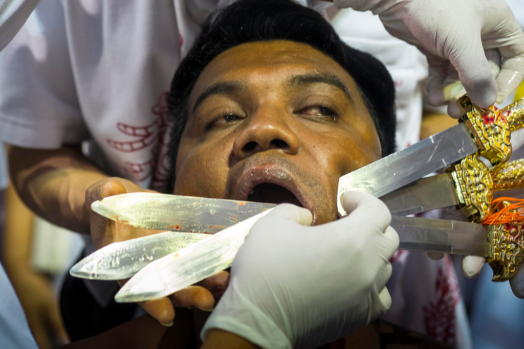 . A devotee has his faced pierced with daggers outside Jui Tui Chinese Shrine on September 30, 2014 in Phuket, Thailand. (Photo by David Longstreath/Getty Images)