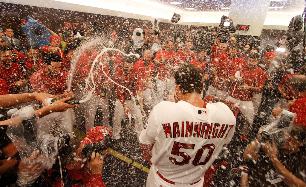 . Teammates spray St. Louis Cardinals starting pitcher Adam Wainwright with champagne in the clubhouse after Game 5 of the National League Division Series between the St. Louis Cardinals and the Pittsburgh Pirates on Wednesday, Oct. 9, 2013, at Busch Stadium in St. Louis.   (AP Photo/post-dispatch.com, Chris Lee)