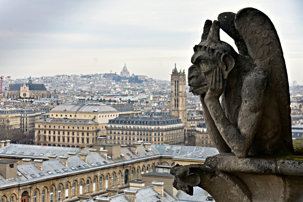 Gargoyle on Notre Dame Cathedral tower overlooking the city in Paris France
