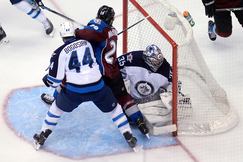 . Nathan MacKinnon (29) of the Colorado Avalanche gets checked by Zach Bogosian (44) of the Winnipeg Jets inside the crease as a shot by John Mitchell (7) goes into the net past Al Montoya (35) during the first period. (Photo by AAron Ontiveroz/The Denver Post)