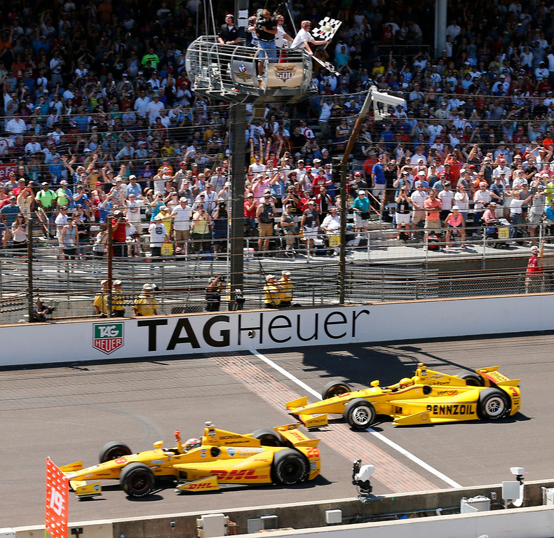 . Ryan Hunter-Reay celebrates after crossing the finish line take the checkered flag in front of Helio Castroneves, of Brazil, to win the 98th running of the Indianapolis 500 IndyCar auto race at the Indianapolis Motor Speedway in Indianapolis, Sunday, May 25, 2014. (AP Photo/Dave Parker)