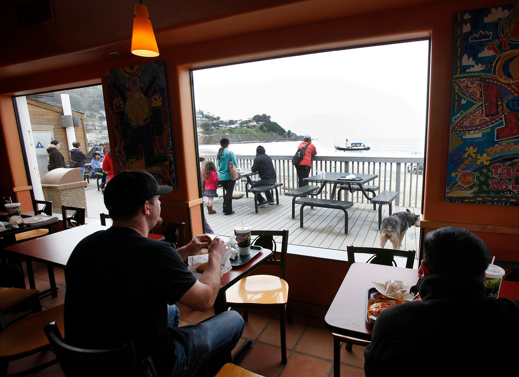 . Diners at Taco Bell enjoy lunch as police deal with a stolen 82-foot-long sailboat that ran aground on Linda Mar Beach in Pacifica, Calif., Monday morning March 4, 2013. The boat had been reported stolen from a Sausalito marina earlier. The three people aboard were all rescued and arrested. (Karl Mondon Photo)