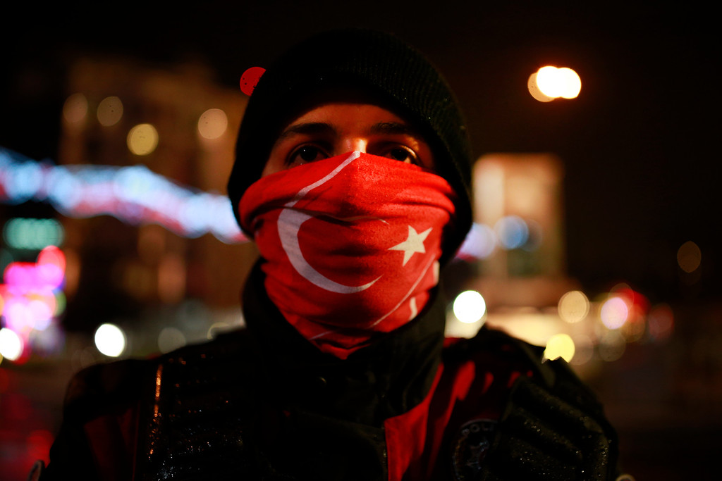 . A man wearing a Turkish flag scarf participates in New Year\'s cerebrations in Istanbul\'s Ortakoy district by the Bosphorus, during New Year\'s cerebrations, late Saturday, Dec. 31, 2016. (AP Photo/Emrah Gurel)