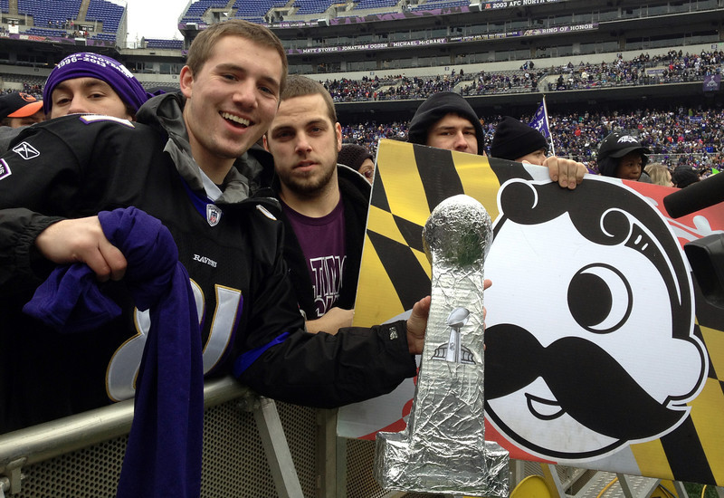 . Sam Muffoletto, 21, and Phil Luzi, 21, hold up signs and a home-made Super Bowl trophy as they wait for the start of Baltimore\'s celebration for the Super Bowl champion Baltimore Ravens at Ravens stadium on Tuesday, Feb. 5, 2013.  Officials expect about 100,000 people to attend the events. (AP Photo/Alex Dominguez)