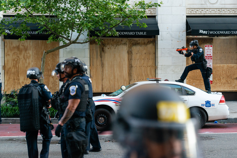 A police officer aims a non-lethal weapon after firing at protesters in Washington, DC on May 31, 2020.