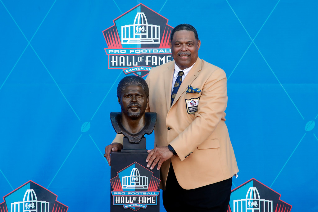 . Former NFL player Robert Brazile poses with a bust of himself during an induction ceremony at the Pro Football Hall of Fame Saturday, Aug. 4, 2018, in Canton, Ohio. (AP Photo/Gene J. Puskar)