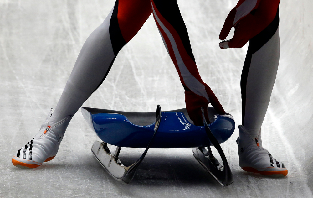 . Reinhard Egger of Austria picks up his sled after finishing his second run during the men\'s singles luge competition at the 2014 Winter Olympics, Saturday, Feb. 8, 2014, in Krasnaya Polyana, Russia. (AP Photo/Dita Alangkara)