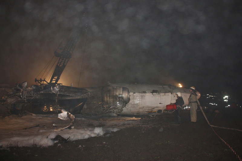 . Firefighters work near the damaged twin-engined Antonov turboprop plane, which broke up during an emergency landing the day before, near the landing strip of the airport in Donetsk in this handout photo released to Reuters February 14, 2013. At least five people were killed when a plane carrying supporters to a European soccer match in eastern Ukraine overshot the runway and broke up when it attempted an emergency landing late on Wednesday, officials said. The twin-engined Antonov turboprop was bringing 45 passengers and crew on a charter flight from the Black Sea coastal city of Odessa to Donetsk - most of them fans looking forward to attending a Champions League clash between the Ukrainian home team Shakhtar and Germany\'s Borussia Dortmund.  REUTERS/State Emergency Service of Ukraine/Handout