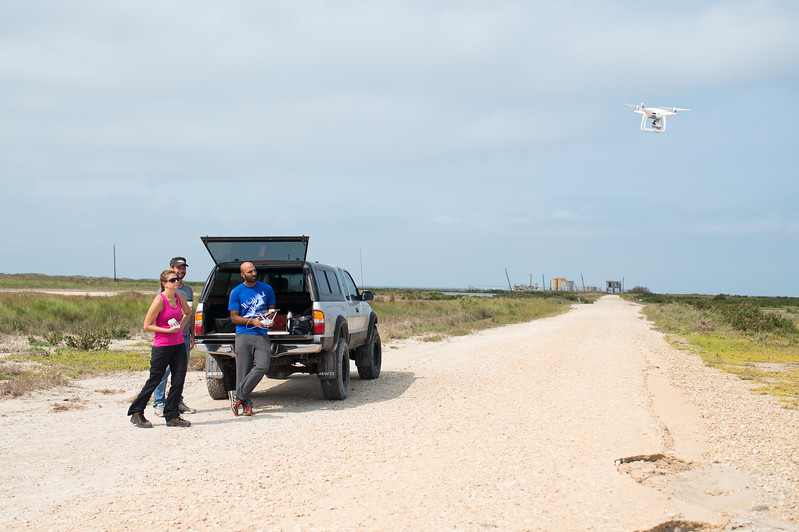 Melanie Gingrass (left), Jake Berryhill, and Yeoshua Cohen use an UAV (Unmanned Air Vehicle) to collect aerial imagery that will be used to survey the marshes on Mustang Island.