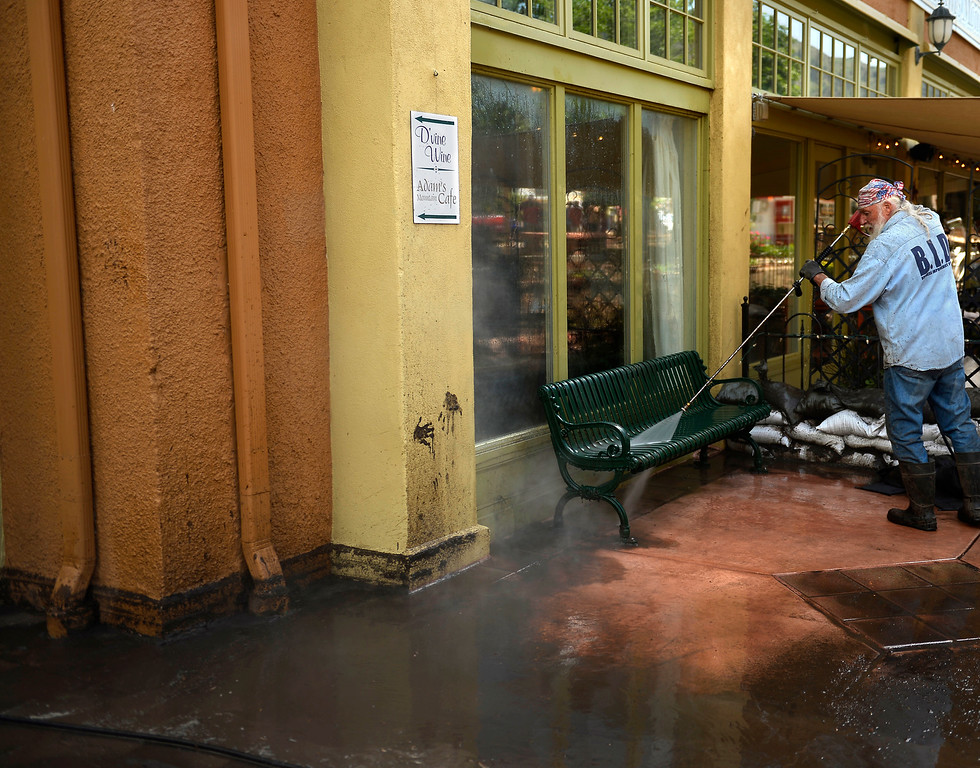 . Manitou Springs, CO. - July 02: Hawk with the Business Improvement District washing down Adams Mountain Cafe after a flash flood washed through houses, streets and businesses when a downpour over the Waldo Canyon burn scar in El Paso County July 02, 2013 Manitou Springs, Colorado. (Photo By Joe Amon/The Denver Post)