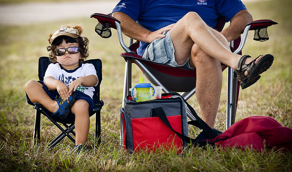 """. 2-year-old Avery Draper hunkers down next to his grandpa Bruce Draper, both of Ontario, Canada, as they watch players run drills during spring training at Hammond Stadium in Fort Myers, Fla., on Friday, February 21, 2014. \""""He was a little whiny by the dugout,\"""" said Bruce, who brought Avery to a quieter area. (Pioneer Press: Ben Garvin)"""
