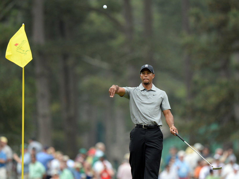 . Tiger Woods of the US tosses his ball to his caddie during the first round of the 77th Masters golf tournament at Augusta National Golf Club on April 11, 2013 in Augusta, Georgia. DON EMMERT/AFP/Getty Images