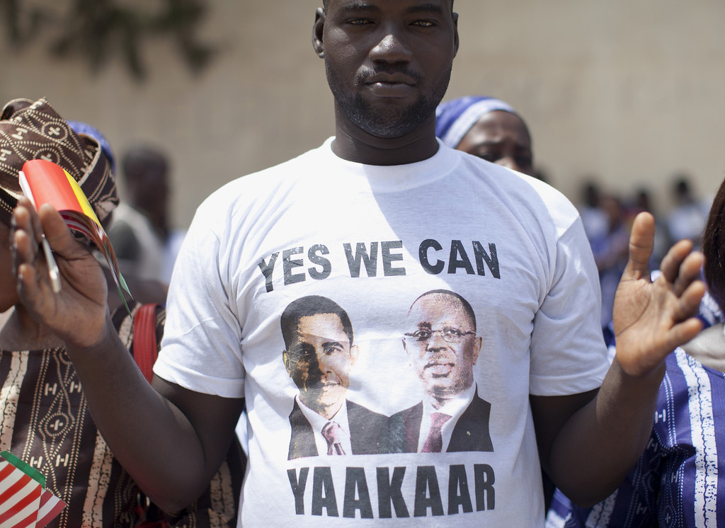""". A man wearing a t-shirt with the images of President Barack Obama and Senegalese President Macky Sall that says \""""Yes We Can Yaakaar\"""", yaakaar meaning hope, stands outside the all-girls Martin Luther King Middle School during a visit by first lady Michelle Obama and Senegal\'s first lady Mariame Faye Sall, Thursday, June 27, 2013, in Dakar, Senegal. (AP Photo/Carolyn Kaster)"""