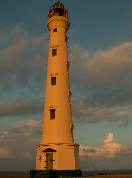 The California Lighthouse sits on a hilltop perch at Aruba's northermost tip. It's active days are over; the beacon itself has been closed to the public for a number of years, ever since someone committed suicide by jumping from its summit. The surrounding area features some of the island's most spectacular scenery--gentle sand dunes, rocky coral shoreline and turbulent waves.