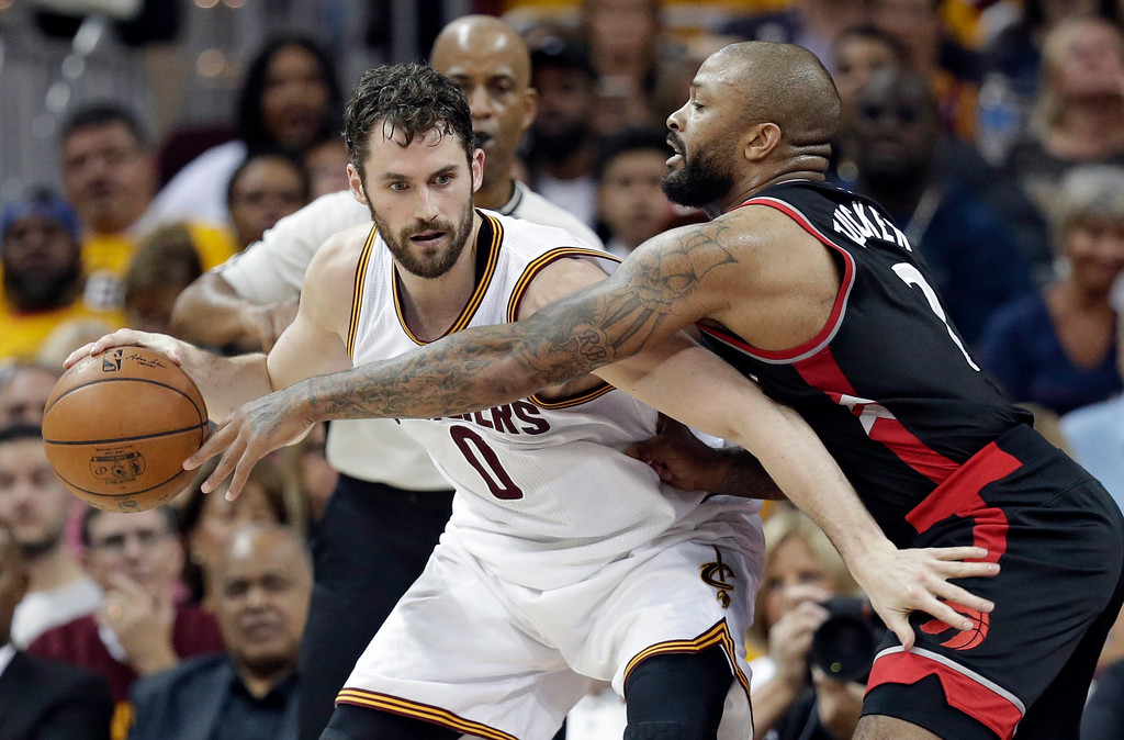 . Toronto Raptors\' P.J. Tucker, right, reaches in against Cleveland Cavaliers\' Kevin Love (0) in the first half in Game 1 of a second-round NBA basketball playoff series, Monday, May 1, 2017, in Cleveland. The Cavaliers won 116-105. (AP Photo/Tony Dejak)