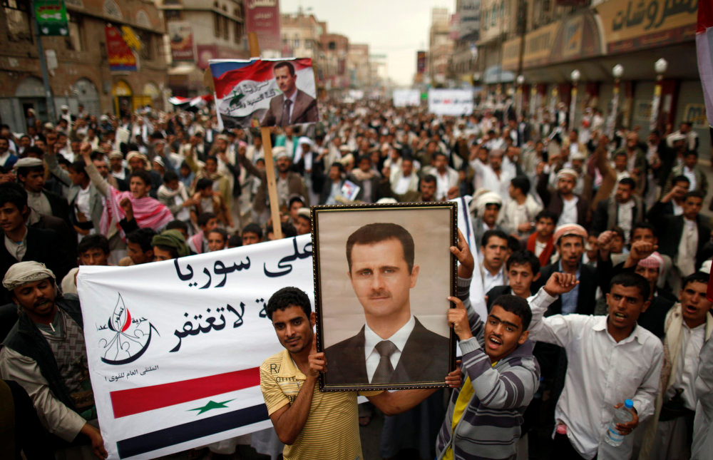 . Shi\'ite anti-government protesters carry posters of Syrian President Bashar al-Assad during a demonstration against Israeli air strikes in Syria, in Sanaa May 10, 2013. REUTERS/Khaled Abdullah