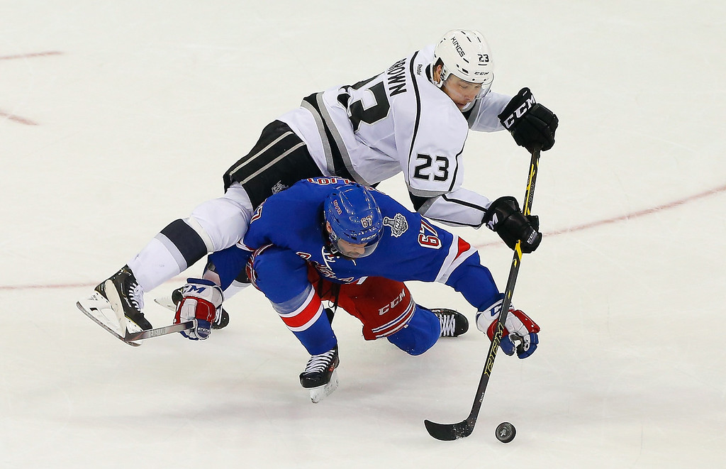 . Dustin Brown #23 of the Los Angeles Kings collides with Benoit Pouliot #67 of the New York Rangers during the second period of Game Three of the 2014 NHL Stanley Cup Final at Madison Square Garden on June 9, 2014 in New York, New York.  (Photo by Jim McIsaac/Getty Images)