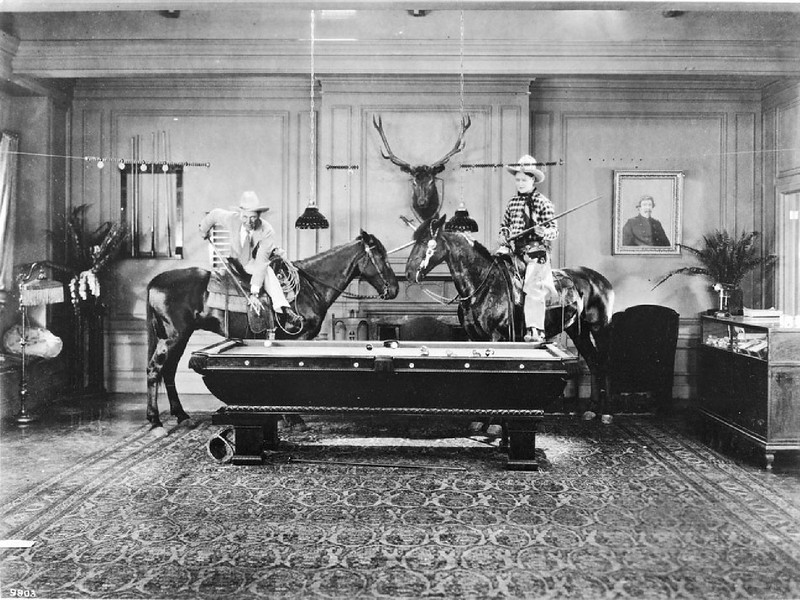 Two men playing a game of pool on horseback inside the home of Eugene Plummer, ca.1920