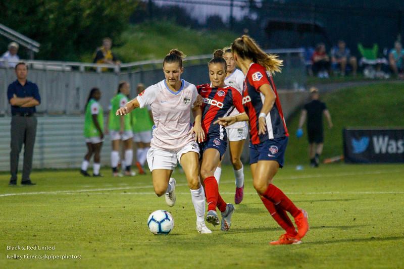 Houston Dash midfielder Haley Hanson (9) fights off Washington Spirit forward Mallory Pugh (11) at Maureen Hendricks Field in Boyds, MD, on July 20, 2019.