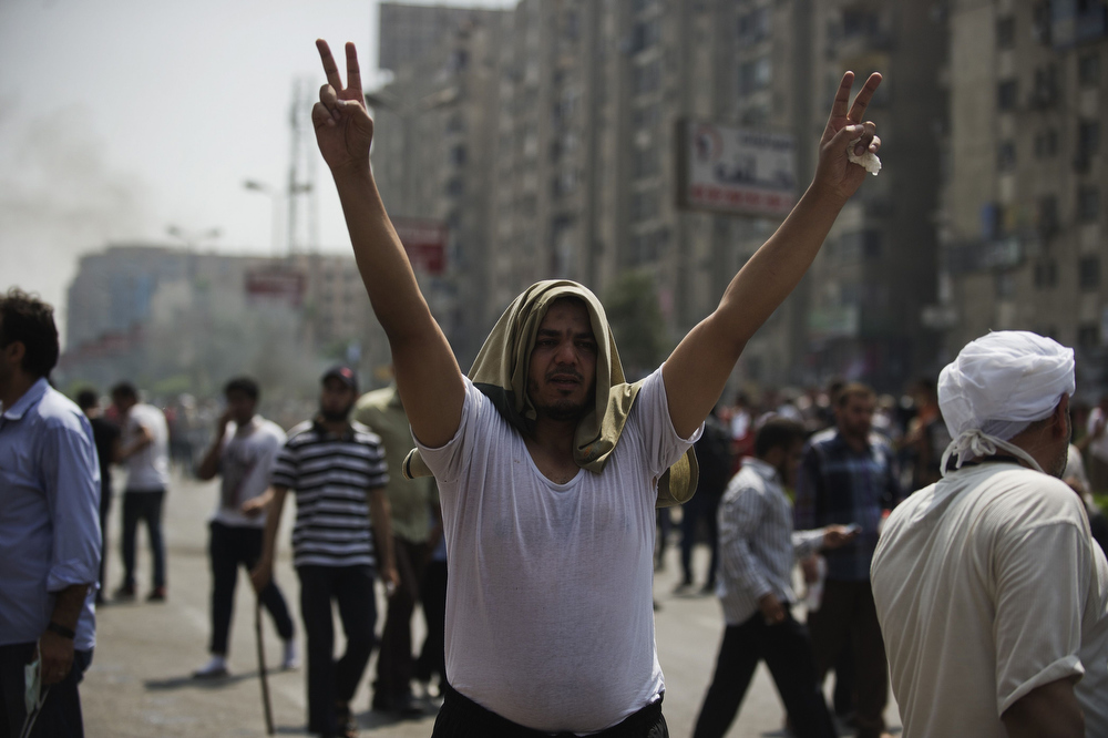 . A supporter of Egypt\'s ousted president Mohamed Morsi gestures during clashes with riot police on a street leading to Rabaa al-Adawiya square in Cairo on August 14, 2013, as security forces backed by bulldozers moved in on two huge pro-Morsi protest camps, launching a long-threatened crackdown that left dozens dead. The clearance operation began shortly after dawn when security forces surrounded the sprawling Rabaa al-Adawiya camp in east Cairo and a similar one at Al-Nahda square, in the centre of the capital.  GIANLUIGI GUERCIA/AFP/Getty Images