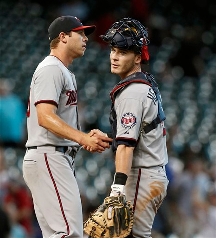 . Minnesota Twins relief pitcher Casey Fien and catcher Chris Herrmann (12) celebrate after the final out against the Houston Astros in the ninth inning. (AP Photo/Bob Levey)