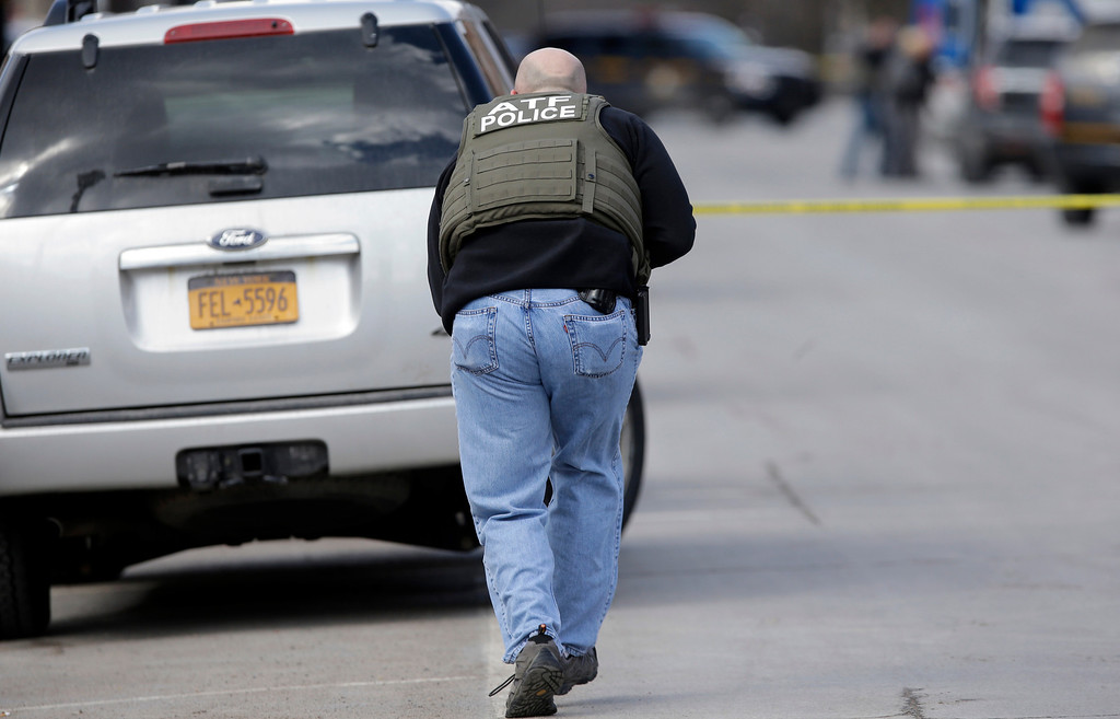 . Law enforcement officers take cover along Main Street in Herkimer, N.Y. Wednesday March 13, 2013, when shots were fired while searching for a suspect in two shootings that killed four and injured at least  two. (AP Photo/Mike Groll)