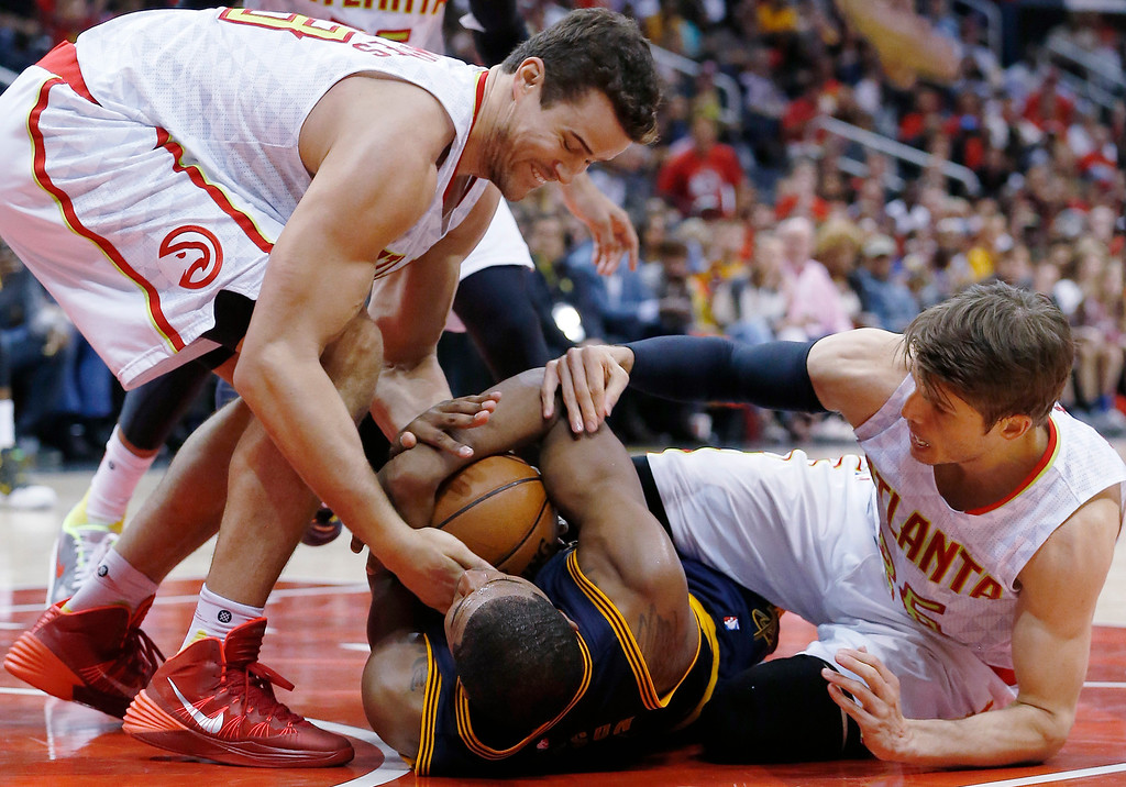 . Cleveland Cavaliers center Tristan Thompson (13) holds on to the ball as Atlanta Hawks guard Kyle Korver, right, and Atlanta Hawks forward Kris Humphries work to get the ball in the second half of Game 3 of the second-round NBA basketball playoff series, Friday, May 6, 2016, in Atlanta. (AP Photo/John Bazemore)