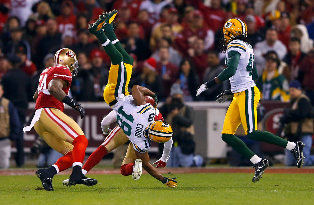 . Green Bay Packers Randall Cobb (2nd R) is tackled by San Francisco 49ers Perrish Cox (2nd L) between 49ers Larry Grant (L) and Packers M.D. Jennings (R) in the second quarter during their NFL NFC Divisional playoff football game in San Francisco, California, January 12, 2013. REUTERS/Mike Blake
