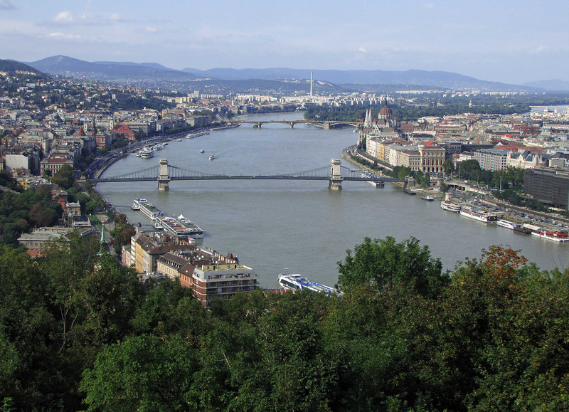 00-Danube, Chain Bridge, Parliament (on the right), and Margaret Island (the trees in the river). Taken from a viewpoint below the Citadel. Buda (the hilly city) is on the left side of the river. Pest (the flat city) is on the right.