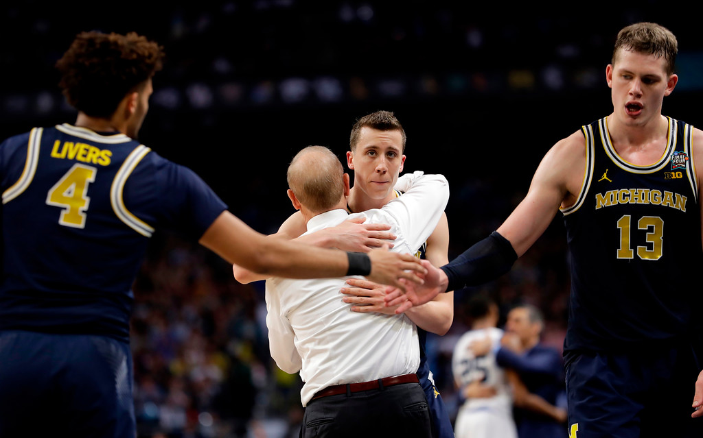 . Michigan\'s Duncan Robinson hugs head coach John Beilein during the second half in the championship game of the Final Four NCAA college basketball tournament against Villanova, Monday, April 2, 2018, in San Antonio. (AP Photo/Eric Gay)