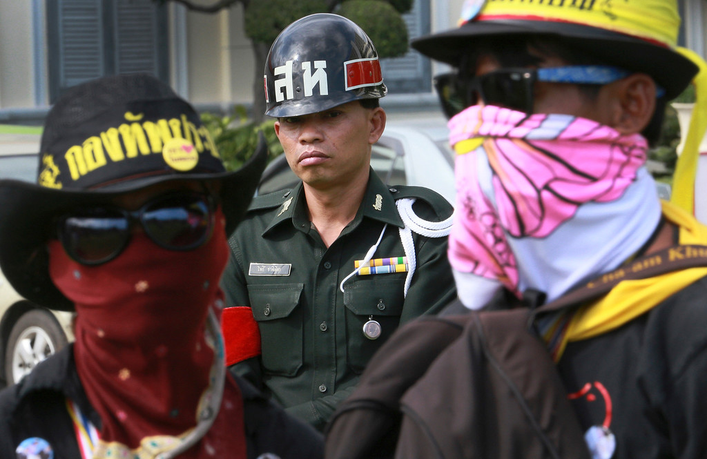 . A Thai soldier, center, stands behind masked protesters at the Royal Thai Army compound in Bangkok, Thailand, Friday, Nov. 29, 2013. Protesters stormed into the national army headquarters on Friday, breaking into their latest high-profile target in a bid to topple Prime Minister Yingluck Shinawatra. (AP Photo/Wason Wanichakorn)
