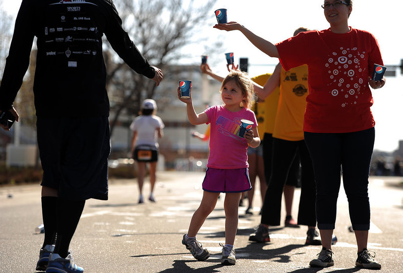 . With only 1/2 mile left to go, 4 year old Aubrey Spain, in pink, helped hand out water to runners. The 31st annual Cherry Creek Sneak had all sorts of distances for this year\'s race.  The Sneak, as it is affectionately named, had a 10 mile, 5 mile, 3.1 mile or 5K, a 1.5 mile Denver\'s 7 Sprint, and a kid\'s fun run for thousands of competitors, runners and walkers that turned out in the Cherry Creek neighborhood of Denver, CO on April 28, 2013.  The race is always held the last Sunday in April. This year participants cheered the national anthem and observed a moment of silence for victims of the Boston Marathon bombing at the start of each race. (Photo by Helen H. Richardson/The Denver Post)