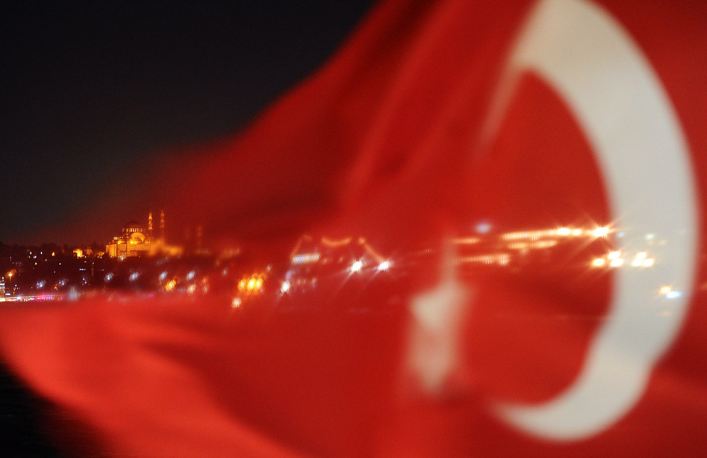 . A Turkish national flag partially hides the Suleymaniye Mosque onboard a ferry passing from the Anatolian to the European side of Istanbul on October 9, 2013.      BULENT KILIC/AFP/Getty Images