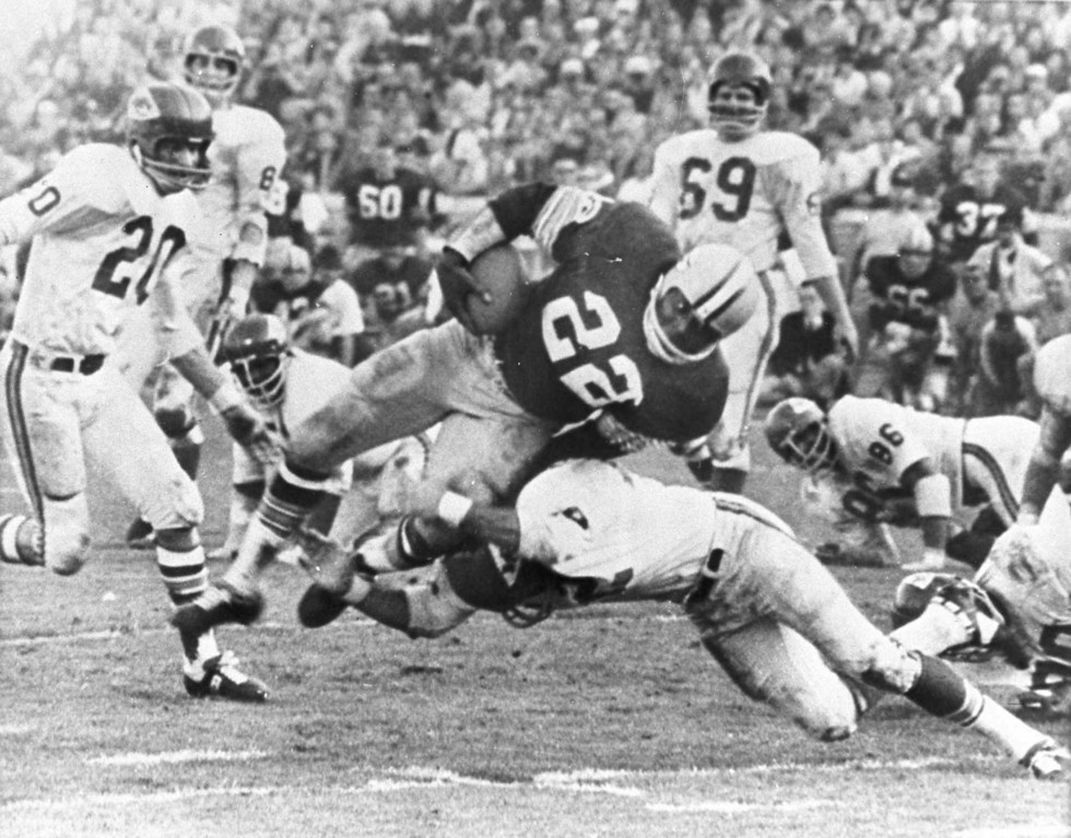 . The Packers\' Klijah Pitts (22) goes over right tackle to the Chiefs\' five-yard line, a six-yard gain, before being brought down by Kansas City\'s Johnny Robinson in the fourth quarter of the Super Bowl game in Los Angeles Jan. 15, 1967.  Three plays later Pitts went over for the touchdown as the Packers beat the Chiefs 35 to 10.  Others include Bobby Hunt (20) and Sherrill Headrick (69).  (AP Photo)