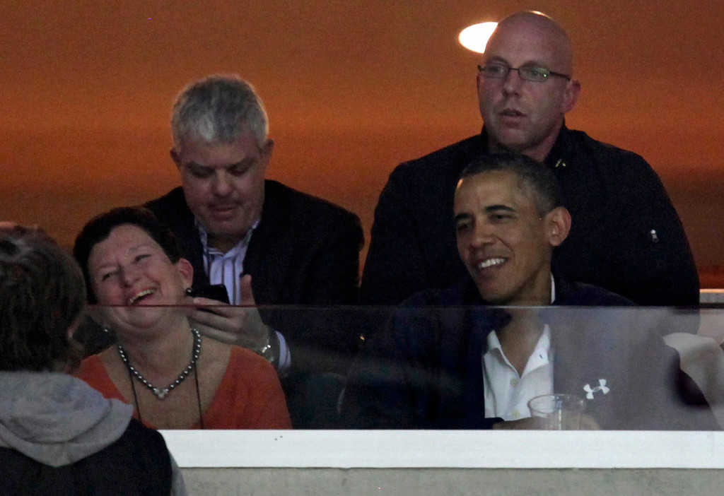 . U.S. President Barack Obama (R) watches an NCAA basketball game between Syracuse Orange and Marquette Golden Eagles in Washington March 30, 2013. REUTERS/Yuri Gripas
