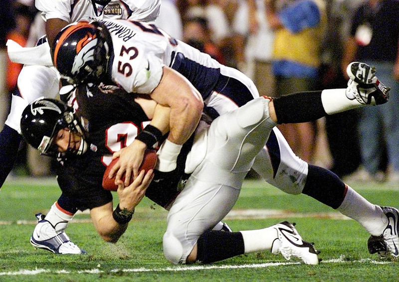 . Atlanta Falcons quarterback Chris Chandler (bottom) is sacked by Denver Broncos linebacker Bill Romanowski in the first quarter of Super Bowl XXXIII, January 31, 1999 at Pro Player Stadium in Miami, Florida. STEPHEN JAFFE/AFP/Getty Images