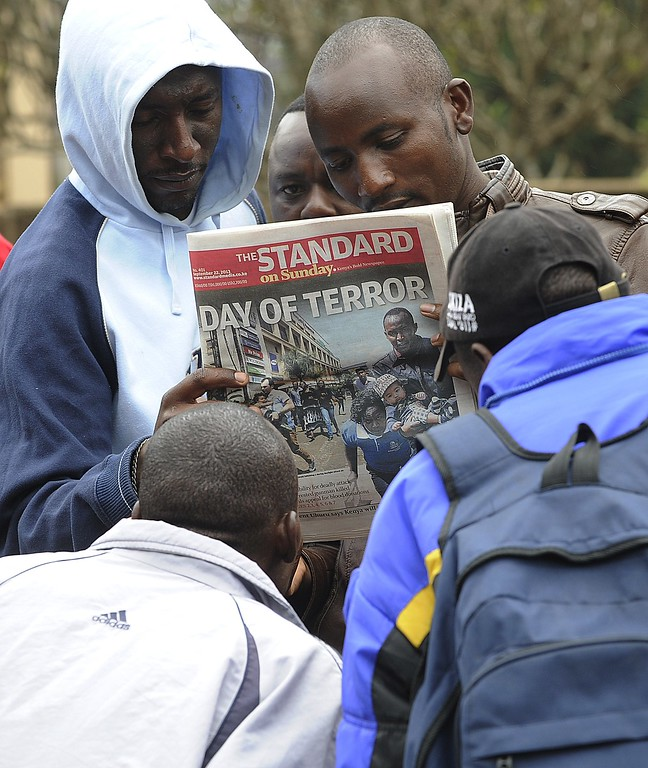 . Kenyans look on September 22, 2013 at a local daily newspaper with the front page featuring the bloodbath at the Westgate mall in Nairobi.  AFP PHOTO / SIMON  MAINA/AFP/Getty Images