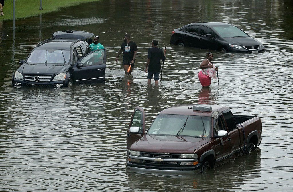 . People walk among stalled cars in a neighborhood flooded by Tropical Storm Harvey on Sunday, Aug. 27, 2017, in Houston, Texas. (AP Photo/Charlie Riedel)