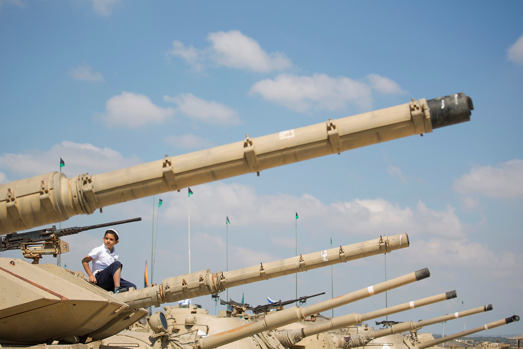 . A boy sit on a tank on display at the Armored Corps memorial, before a ceremony marking the annual Memorial Day for soldiers and civilians killed in more than a century of conflict between Jews and Arabs, in Latrun near Jerusalem, Israel, Wednesday, May 11, 2016. Israel came to a standstill on Wednesday as sirens wailed across the country on its annual Memorial Day for fallen soldiers and victims of terrorism. (AP Photo/Ariel Schalit)